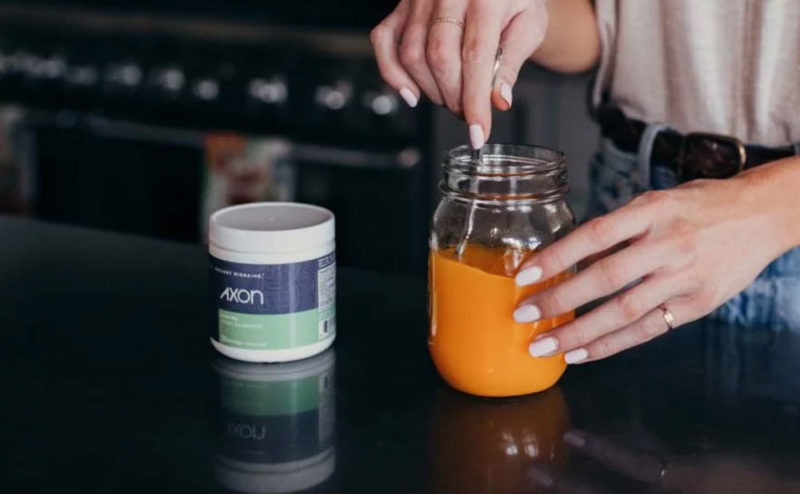 Woman mixing Axon Migraine Supplement Drink Mix