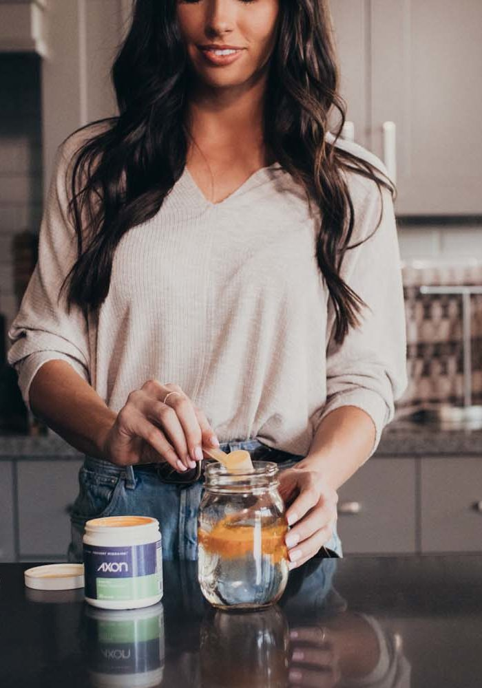 Woman mixing Axon Migraine Supplement Drink Mix in a glass